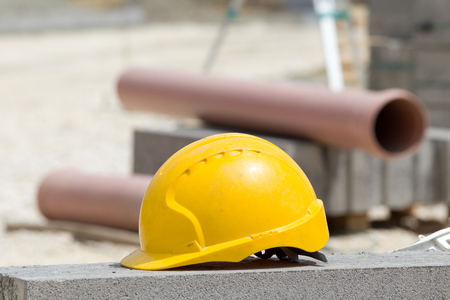 Yellow helmet standing on concrete roadside at construction site. Plastic pipes and roadside blocks in background