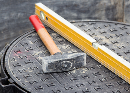 leveling instrument: Close up of hammer and level standing on manhole cover at building site