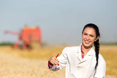 agronomist: Portrait of young smiling woman agronomist in golden wheat field during harvest