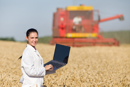 agronomist: Young smiling woman agronomist in white coat holding laptop in golden wheat field during harvest, combine in background