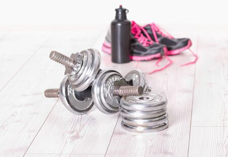 additional training: Sport concept. Close up of two steel dumbbells and pink sneakers and bottle of water in background Stock Photo