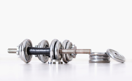 additional training: Sport concept. Close up of two steel dumbbells and extra weight plates in background