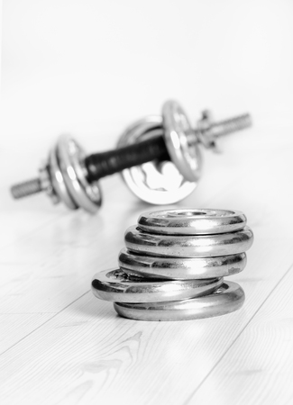 additional training: Close up of metallic extra weight plates on wooden floor and dumbbells in background