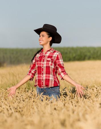 chemise carreaux: Cowgirl avec chemise � carreaux et chapeau noir marche dans un champ de bl� m�r dans le temps de l'�t�
