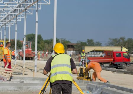 teodolito: ambiente emplazamiento de la obra. Ingeniero que trabaja en teodolito. Los trabajadores y maquinaria de construcción en el fondo Foto de archivo