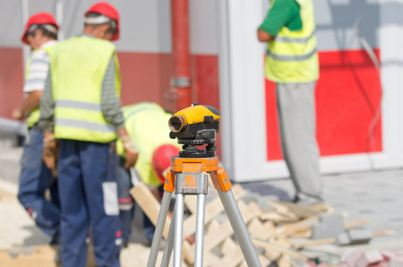 leveling instrument: Theodolite on tripod at building site with workers in background