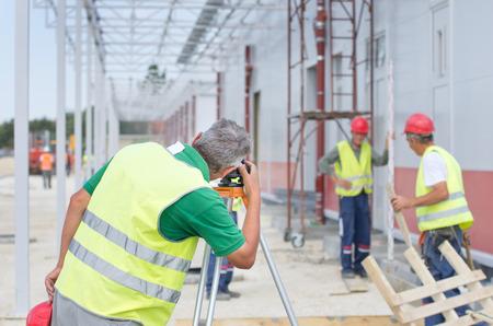 teodolito: Ingeniero de más edad trabajan con el teodolito en el sitio de construcción. Trabajadores en el fondo Foto de archivo
