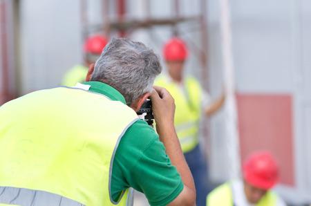 teodolito: Ingeniero de m�s edad trabajan con el teodolito en el sitio de construcci�n. Trabajadores en el fondo Foto de archivo