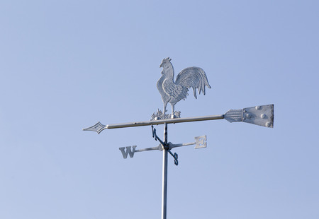 meteorological: White rooster weather vane on the roof