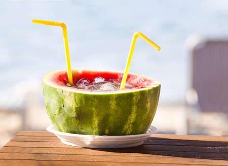 drinks on bar: Exotic soft drink in watermelon peel with two yellow straws on wooden table.