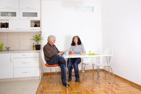 dining: Senior couple sitting in dining room and drinking coffee