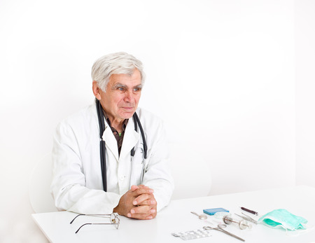 bata blanca: Conceived senior doctor in white coat sitting at table with medical equipment on it Foto de archivo
