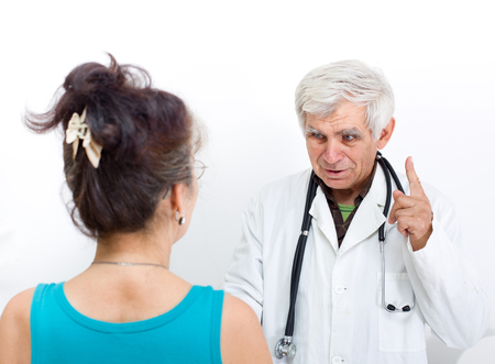 pointing finger up: Senior doctor talking to patient, carrying stethoscope on the neck and pointing finger up Stock Photo