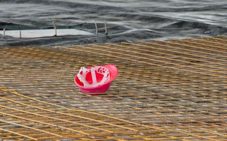 cabeza abajo: Casco rojo de pie en posición invertida sobre malla de refuerzo en obras de construcción