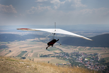 hang glider: Hang glider jump from top of hill, village and field down in background