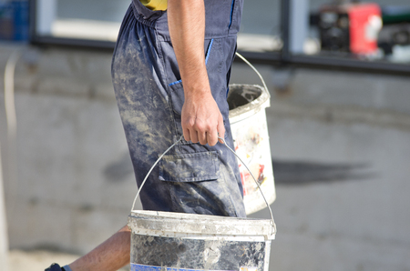 work wear: Construction worker in dirty work wear carrying two buckets with cement Stock Photo