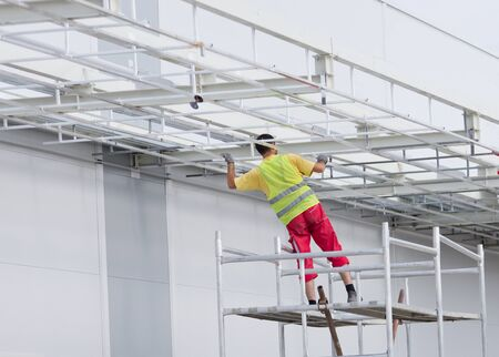 metal structure: Worker standing on scaffolding and painting metal awning at building site