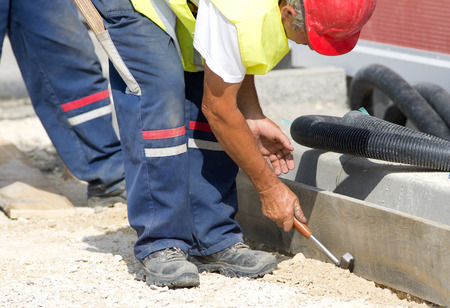 by placing: Construction worker placing wood formwork with hammer at building site Stock Photo