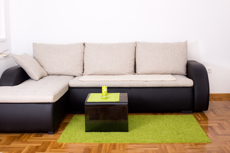 Green Carpet Elegant Small Sofa In The Corner Of Living Room With Black Glass Coffee