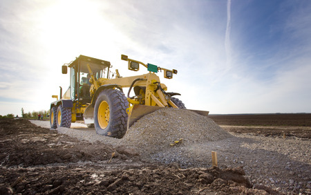 grader: Grader leveling gravel on road construction site