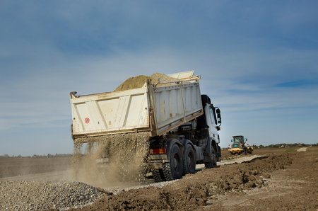 grader: White truck tipping gravel for road construction. Grader working in background Stock Photo