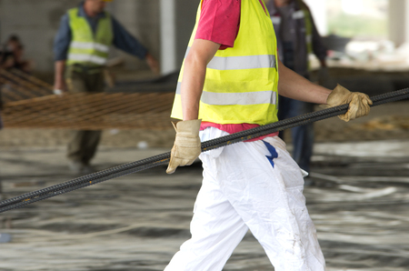 Construction worker carrying reinforcement rods at building site