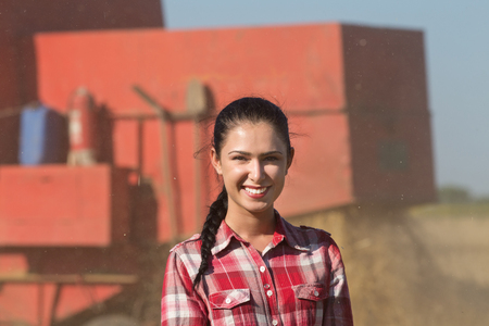 female portrait: Portrait of pretty girl in plaid shirt and with braid smiling in front of combine harvester in the field Stock Photo