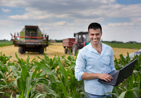farmers: Young attractive farmer with laptop standing in corn field, tractor and combine harvester working in wheat field in background
