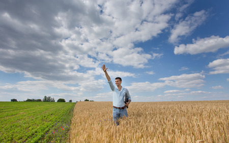 field crop: Satisfied businessman standing in golden barley field with laptop and raised arm Stock Photo