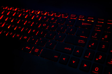 モダンな暗闇の中でゲームのノート パソコンのキーボードのバックライトを赤