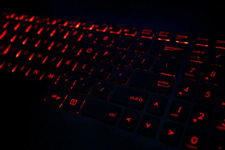 어둠 속에서 게임 노트북의 현대적인 키보드에 빨간 백라이트
