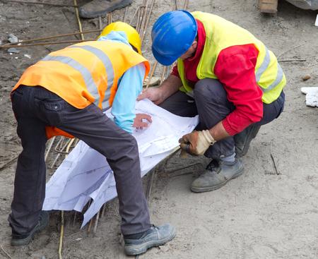 obreros: Dos construcci�n del proyecto de lectura trabajador de planos en el sitio de construcci�n Foto de archivo