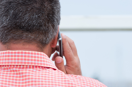 listening back: Rear view of grayish businessman talking on cellphone Stock Photo