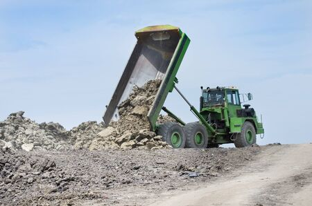 sky scraper: Green dump truck tipping earth from trailer, blue sky in background Stock Photo