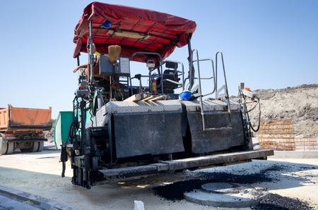 asphalt paving: Paving machine loaded with fresh asphalt preparing for laying finish layer at the road