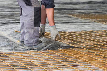 construction mesh: Construction worker installing reinforcement mesh at building site Stock Photo