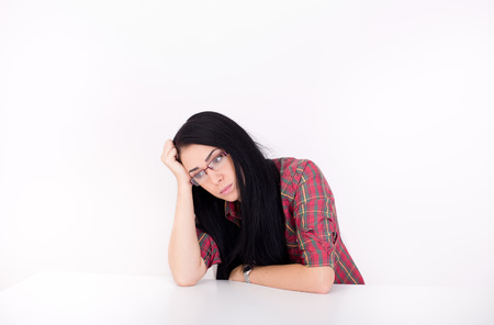 unmotivated: Depressed young woman leaning on arm on the desk. Isolated on white background Stock Photo