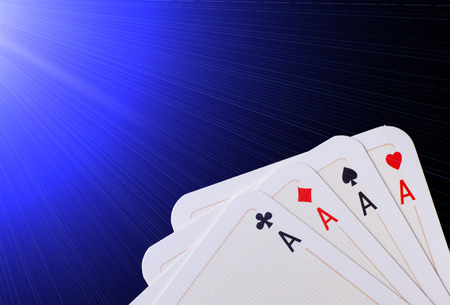 aces: Close up of poker hand of four aces  against blue background