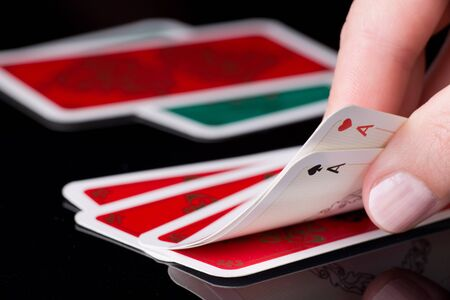 aces: Human hand holding two aces in poker game, cards in background Stock Photo
