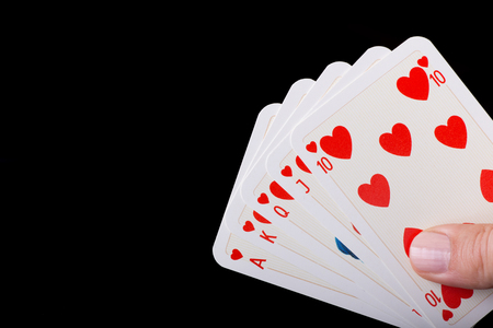 royal background: Poker hand of Royal flush of hearts against black background