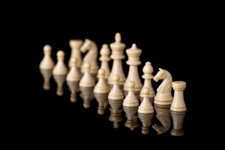 starting position: White chessman on starting position of game. Black background with reflection Stock Photo