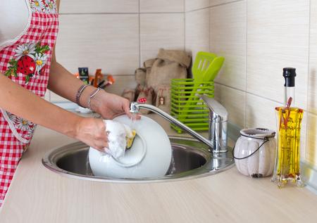 lavandose las manos: Mujer joven con el lavado de platos en el delantal de la cocina moderna