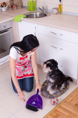 pee pee: Young woman squatting on knees while cleaning after her dog in the kitchen