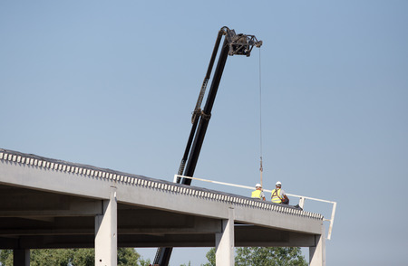 elevator operator: Two construction worker sitting on the edge of the roof while crane is working beside them Stock Photo