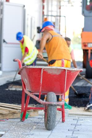 carretilla: Cierre de la carretilla en la obra. Trabajadores de la construcción que trabajan con asfalto y palas en el fondo