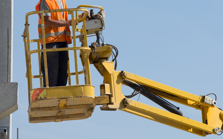 elevator operator: Construction worker operating with lifting security cage for works on height