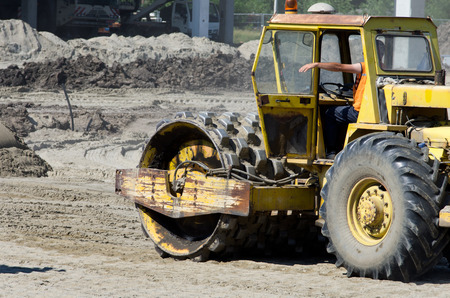 vibroroller: Rusty roll compactor working on sand area at construction site
