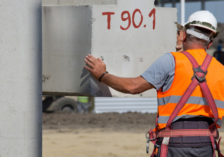 elevator operator: Construction worker placing concrete beam lifted by crane on the building site