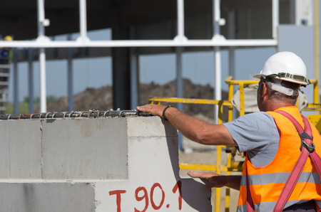 elevator operator: Construction worker standing beside huge concrete beam at building site
