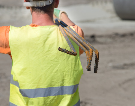 shoulder carrying: Construction worker carrying reinforcement rods on the shoulder. Rear view of man